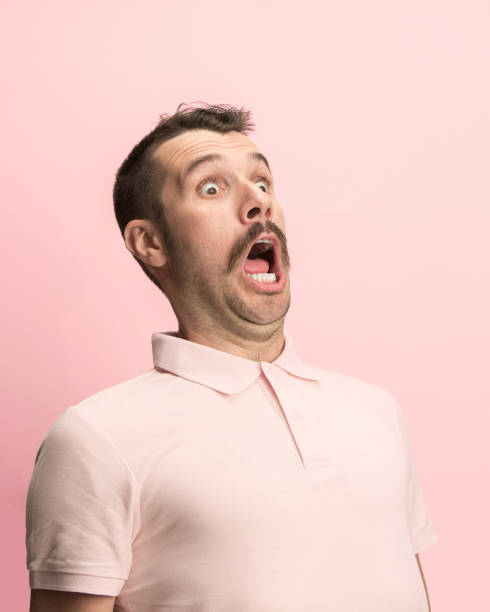 The man screaming with open mouth isolated on pink background, concept face emotion The surprised and astonished young man screaming with open mouth isolated on pink background. concept of shock face emotion bad news stock pictures, royalty-free photos & images