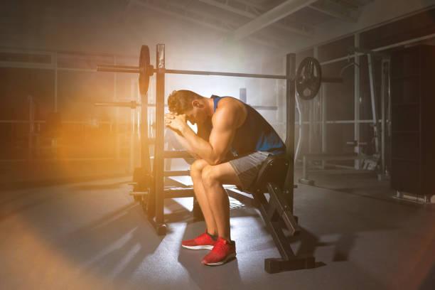 der mann sitzt auf einer bank in der turnhalle auf dem hellen licht hintergrund - mit muskelkater trainieren stock-fotos und bilder