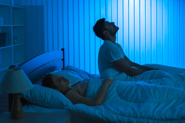The man sit on the bed with an insomnia near woman. night time The man sit on the bed with an insomnia near woman. night time midnight stock pictures, royalty-free photos & images