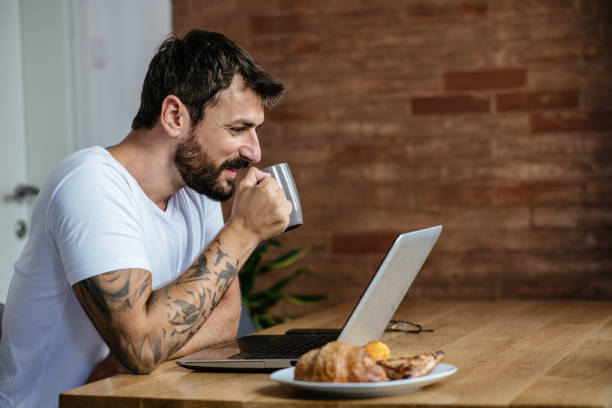 The man sits at a table in the dining room during the morning and has an online meeting with the firm, listening and drinking coffee stock photo