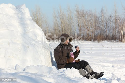 istock The man sitting near an igloo and drinking tea 509561170