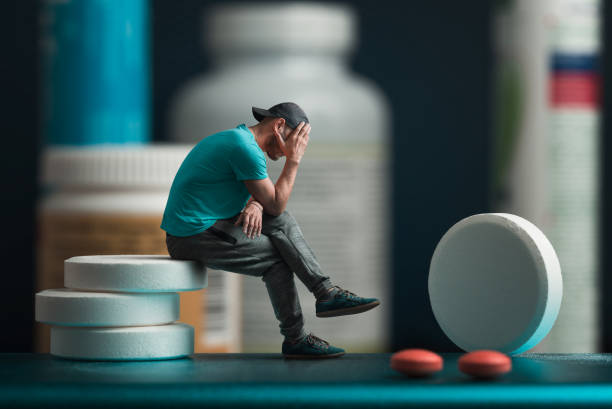 The man sitting on the pills. He's depressed. Flacons of medicines in the background The man sitting on the pills. He's depressed. Flacons of medicines in the background. Collage. erectile dysfunction stock pictures, royalty-free photos & images
