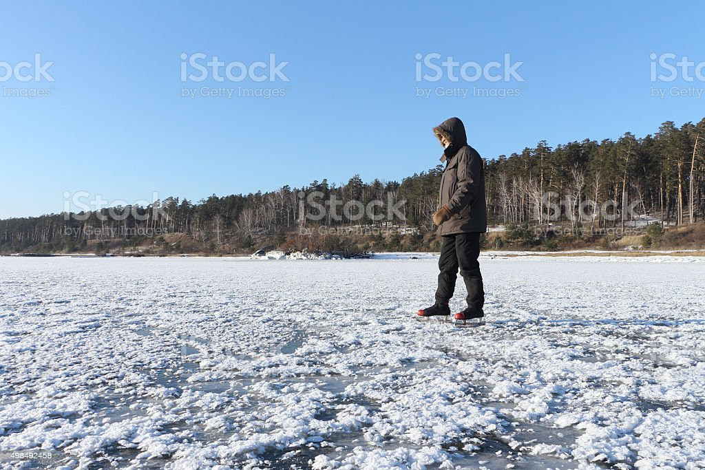 The man skating on the frozen river in the winter stock photo