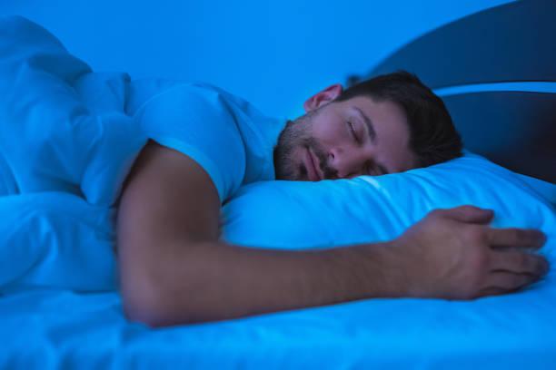 el hombre durmiendo en la cama. noche - man sleeping fotografías e imágenes de stock