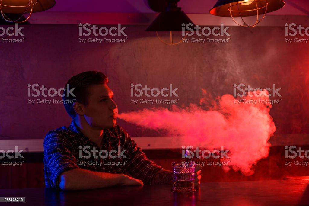 The man smoke an electronic cigarette at the vape shop stock photo