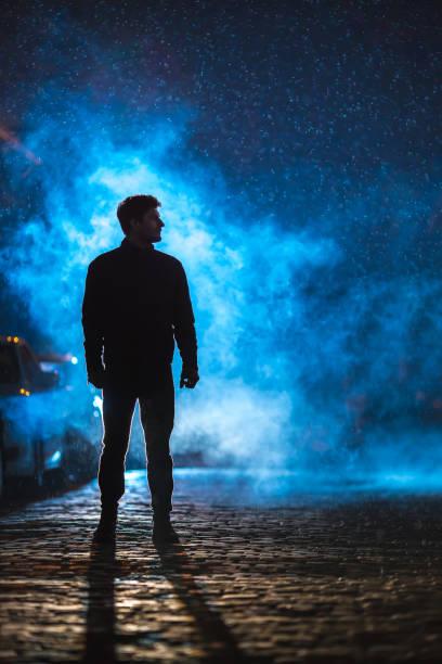 de man staan op de rook straat. avond nacht tijd. telelens geschoten - telelens stockfoto's en -beelden