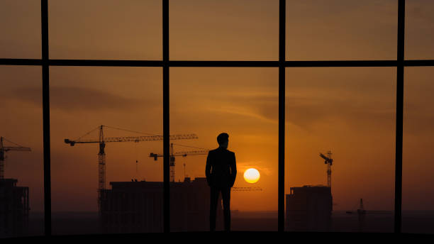 the man standing near the panoramic window on building construction background - man look sky scraper foto e immagini stock
