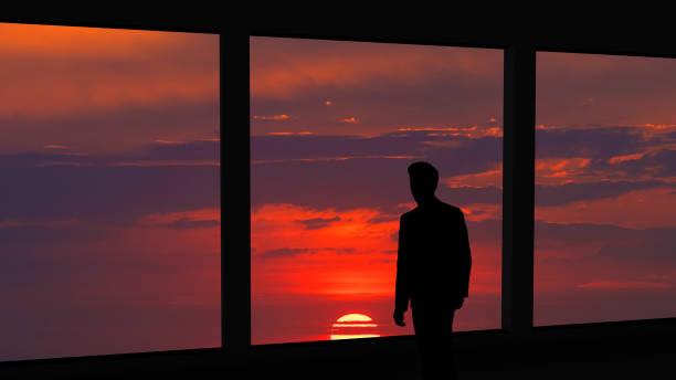 the man standing near the panoramic window on the beautiful sunset background - man look sky scraper foto e immagini stock