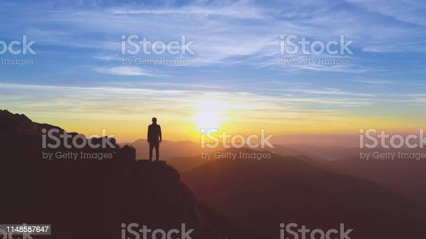 Photo of The man standing on the mountain on the picturesque sunrise background
