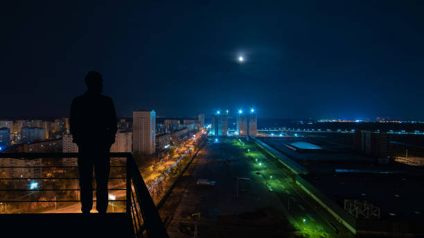 the man standing on the top of building on the night cityscape background - man look sky scraper foto e immagini stock