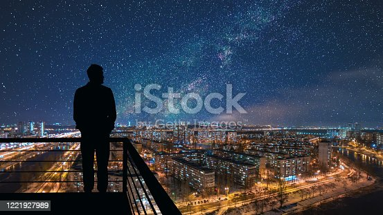 The man standing on the top of building on the starry cityscape background