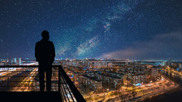 the man standing on the top of building on the starry cityscape background - man look sky scraper foto e immagini stock
