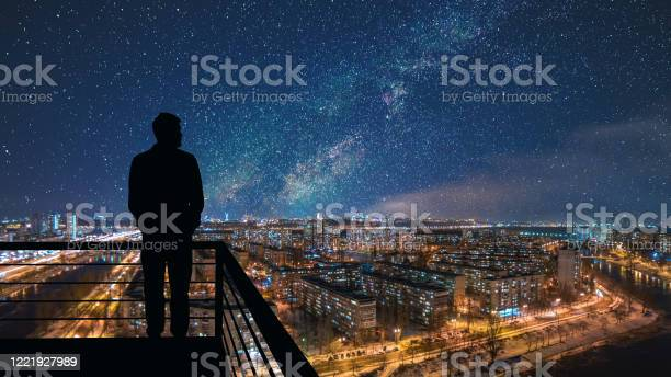 Photo of The man standing on the top of building on the starry cityscape background
