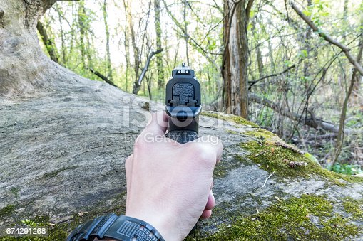 istock The man takes aim from the pistol. Man. Arm. Forest. 674291268