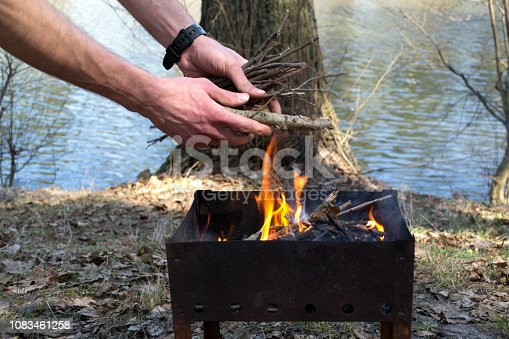 istock The man throws dry branches into the fire. 1083461258
