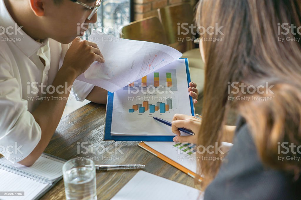 The man turning page of folder, woman pointing at it stock photo