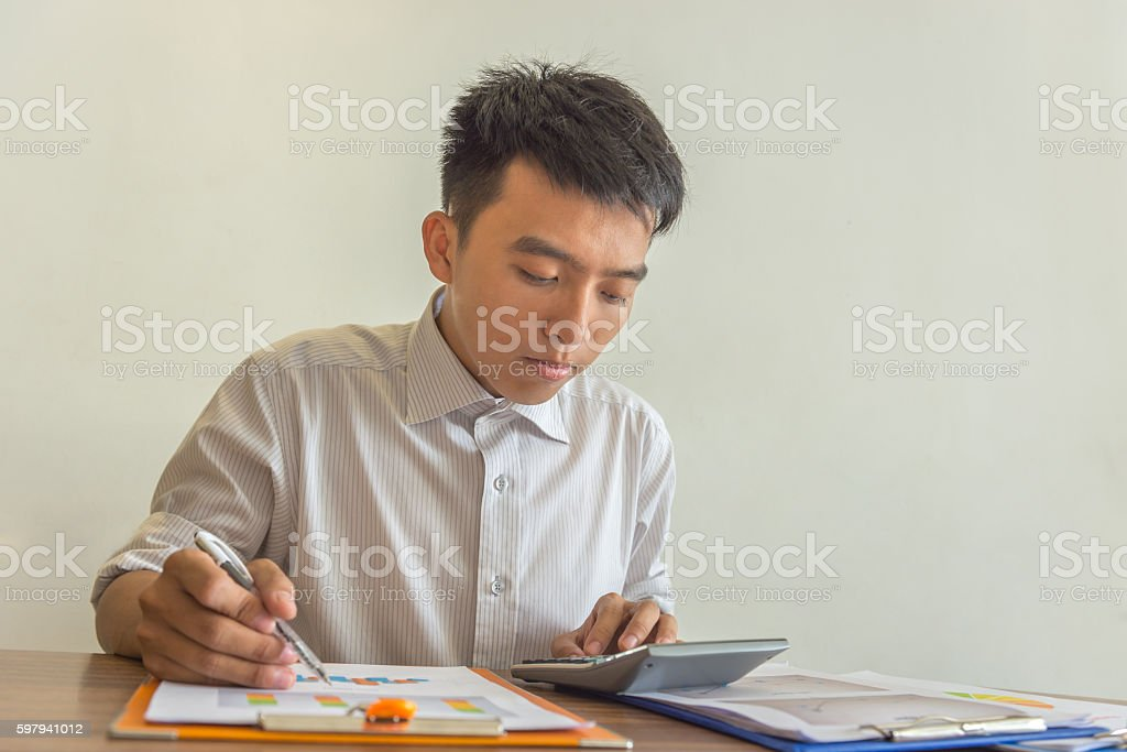 The man using calculator to check the number in report foto royalty-free