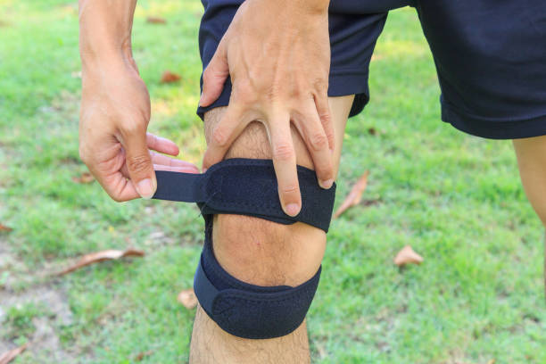 The man wear the Knee Support Brace Patella with sunlight in the park stock photo