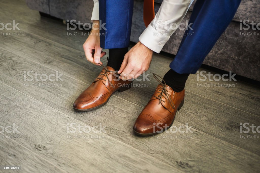 The man wears shoes. Tie the laces on the shoes. Men's style. Professions. To prepare for work, to the meeting. stock photo