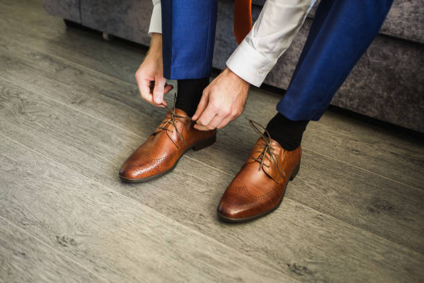 de man draagt schoenen. bind de veters van de schoenen. mannen stijl. beroepen. ter voorbereiding van het werk, aan de vergadering. - shoe stockfoto's en -beelden