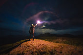 The man with a bright firework stick standing on a mountain. evening night time
