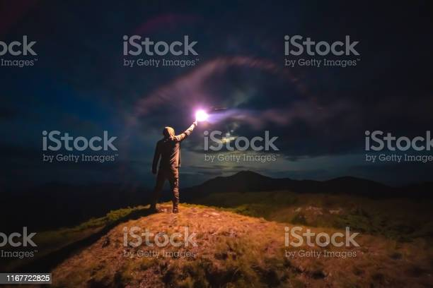 Photo of The man with a bright firework stick standing on a mountain. evening night time