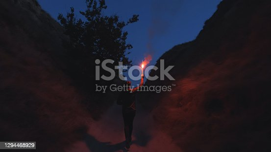 The man with a fire stick walking in the mountains