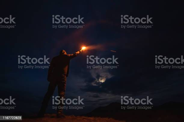 Photo of The man with a firework stick standing on the night mountain