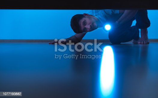 istock The man with a flashlight looking under the bed. evening night time 1077193882