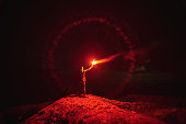 The man with a red firework stick standing on a mountain. evening night time