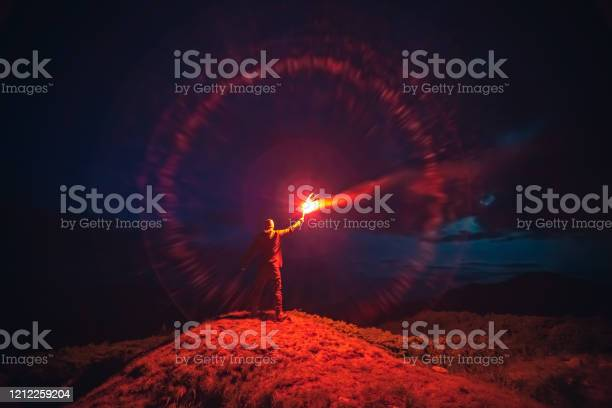 Photo of The man with a red firework stick standing on a mountain. evening night time