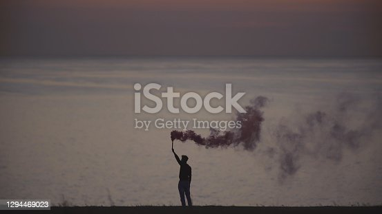The man with a smoke stick standing on the sea coast