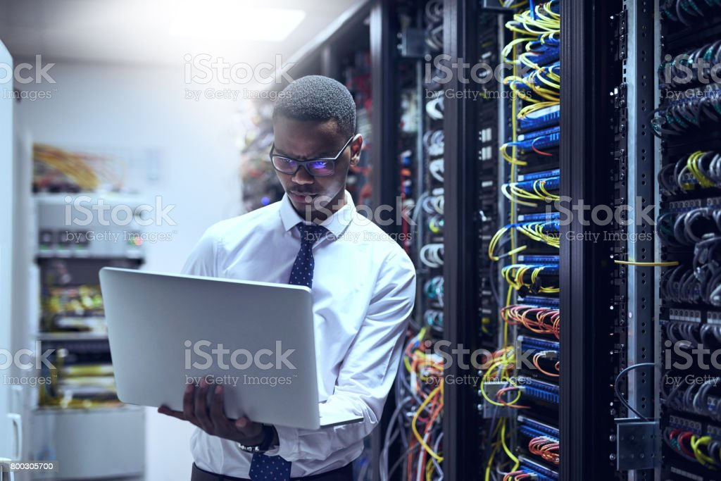 The man with the plan Cropped shot of a IT technician working on his laptop while standing inside of a server room Adult Stock Photo