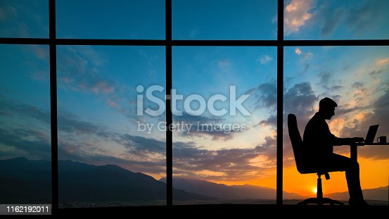 The man working at the table near a window on a mountain sunset background
