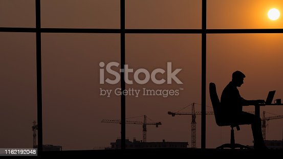 The man working at the table near a window on an industrial city background