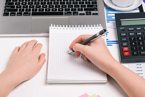 The man writes in a notebook. Workplace with a computer, calculator and financial charts. Preparation of a tax report. Company budget planning. Business and finance concept
