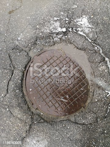 The manhole cover in the asphalt road close up to use as background