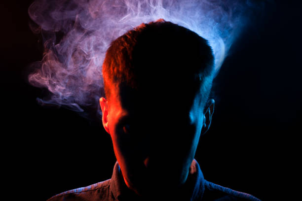 The man's face is hidden in the shadows on a black isolated background with red and blue smoke from the vape. Extraneous thoughts. stock photo