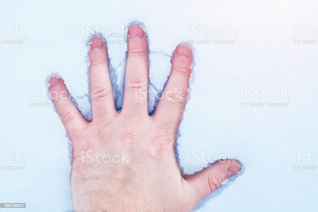 The man's hand touches the snow stock photo