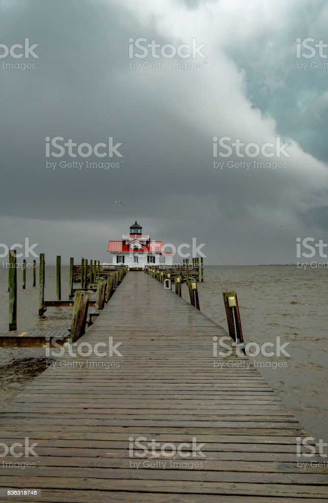 The Manteo Lighthouse and boardwalk in a rainstorm stock photo