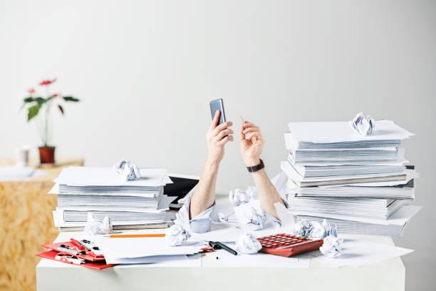 wiele zmiętych dokumentów na biurku zestresowanego męskiego miejsca pracy - duża grupa obiektów zdjęcia i obrazy z banku zdjęć