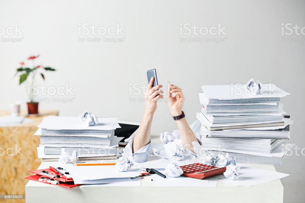 The many crumpled papers on desk of stressed male workplace stock photo