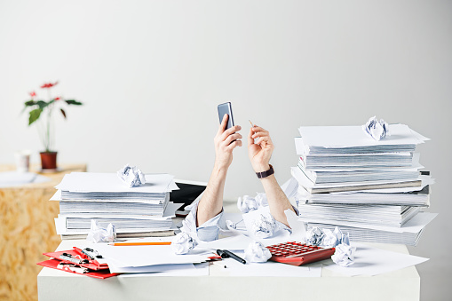 The Many Crumpled Papers On Desk Of Stressed Male Workplace Stock Photo - Download Image Now