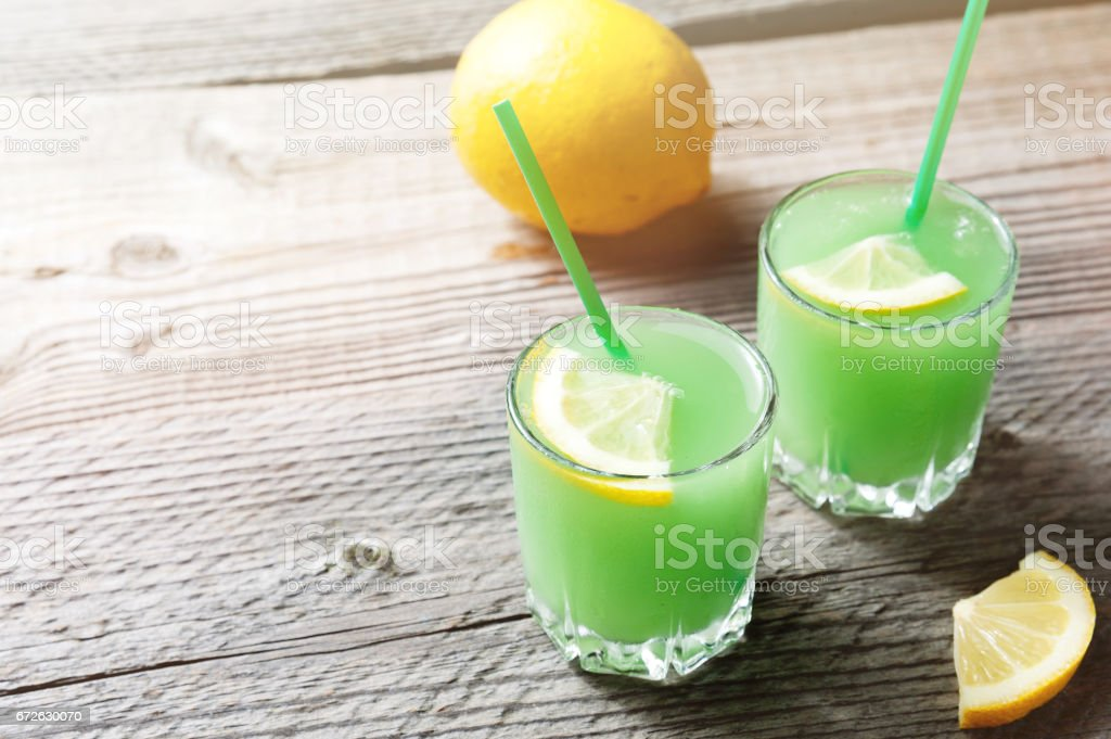 The Margarita cocktail with lemon and ice cubes on old wooden table stock photo