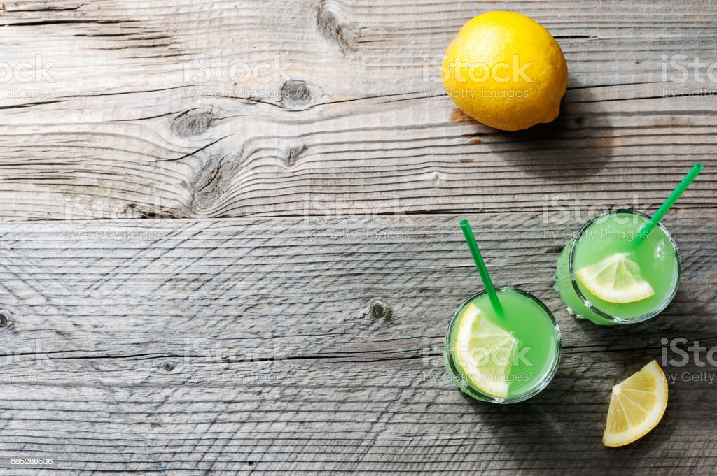 The Margarita cocktail with lemon and ice cubes on old wooden table top view stock photo