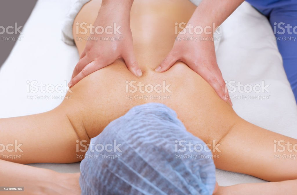 The masseur makes a massage on the back of the patient in the beauty salon. stock photo