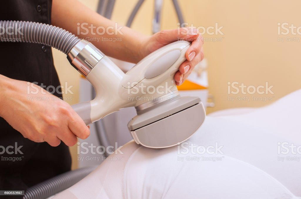 The masseur makes an hardware massage on the patient's legs in a white suit, close-up stock photo