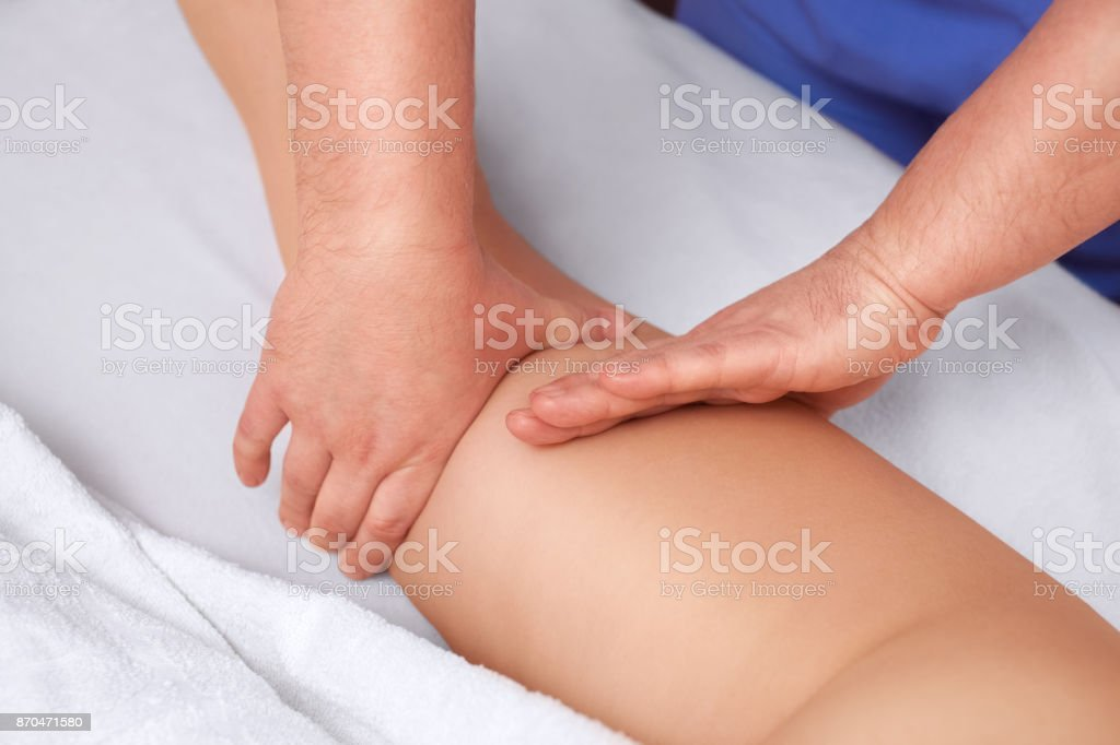 The masseur makes Anti-cellulite massage on the buttock and thighs of the patient stock photo
