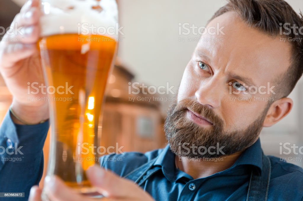The master brewer holding beer glass in his micro brewery Happy master brewer standing in front of copper vat and holding beer glass in his micro brewery, checking quality. Adult Stock Photo