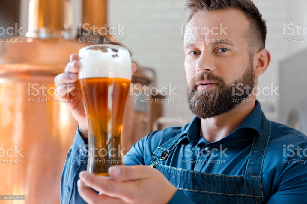 The master brewer holding beer glass in his micro brewery Happy master brewer standing in front of copper vat and holding beer glass in his micro brewery. Adult Stock Photo